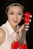 stock photo of ukulele  - Asian American teen girl protrait with ukulele - JPG