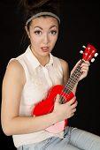 picture of ukulele  - Teen girl model playing ukulele fun expression - JPG