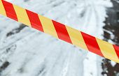 foto of restriction  - Red and yellow striped tape on winter road - JPG
