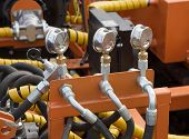 foto of hydraulics  - Hydraulic tubes fittings and levers on control panel of lifting mechanism - JPG