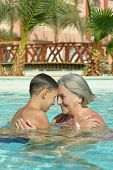 stock photo of grandma  - Happy smiling grandma and grandson in blue pool water - JPG