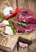 stock photo of beef shank  - Fresh beef steak with aromatic spices on a wooden background - JPG