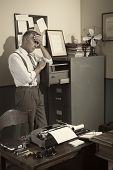stock photo of forehead  - Tired businessman standing next to file cabinet touching his forehead - JPG