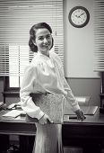 stock photo of secretary  - Cute vintage secretary working at office smiling and holding a folder with paperwork - JPG