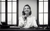 picture of 1950s  - Smiling vintage receptionist working at office desk and smiling - JPG