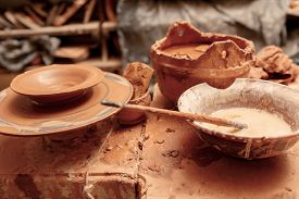 stock photo of pottery  - Art of pottery. Still life of pottery making tools, brush and pottery wheel in clay studio ** Note: Shallow depth of field - JPG