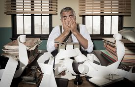 foto of 1950s style  - Desperate accountant head in hands surrounded by bills on paper tape 1950s style office - JPG