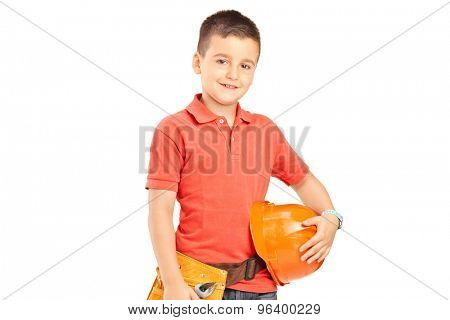 Little boy holding a protective helmet and wearing a tool belt isolated on white background