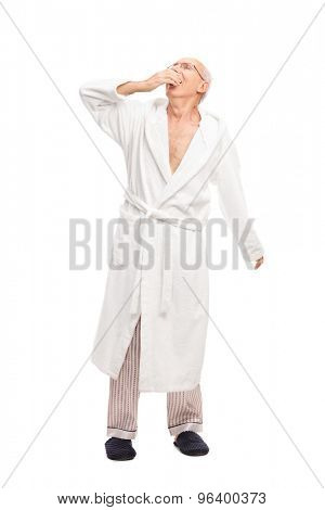 Full length portrait of a sleepy senior man in a white bathrobe yawning isolated on white background