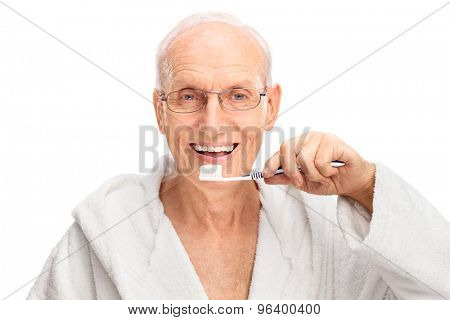 Studio shot of a cheerful senior in a white bathrobe brushing his teeth and looking at the camera isolated on white background