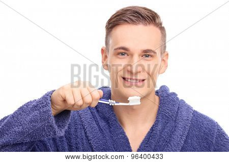 Young man in a blue bathrobe brushing his teeth with a toothbrush and looking at the camera isolated on white background