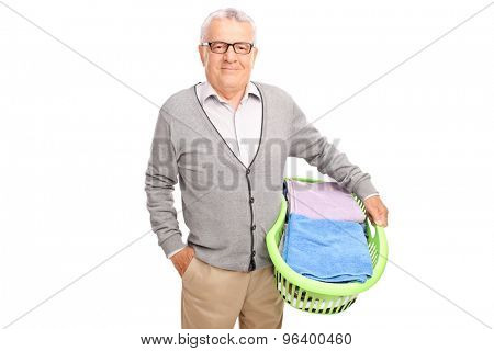 Cheerful senior man holding a laundry basket and looking at the camera isolated on white background