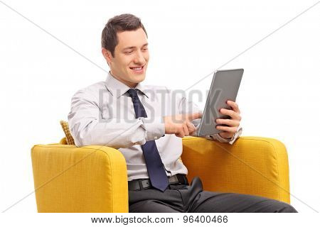 Young businessman working on a tablet seated in a yellow armchair isolated on white background