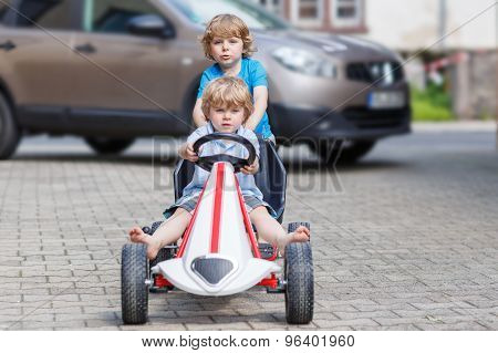 Two Happy Boy Friends Having Fun With Toy Car