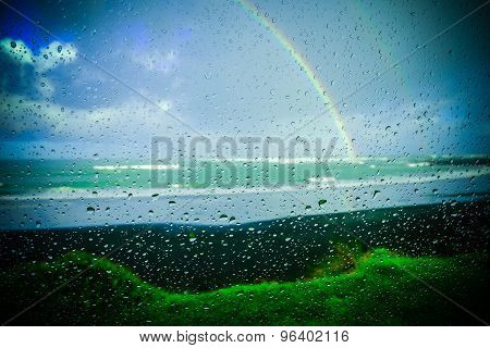 Rainbow Over The Ocean At Rays Rest. New Zealand. Picture Taken Behind Glas With Reflecting Raindrop