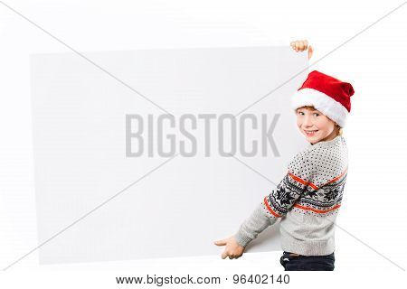Portrait of a boy in christmas hat holding white blank. Isolated