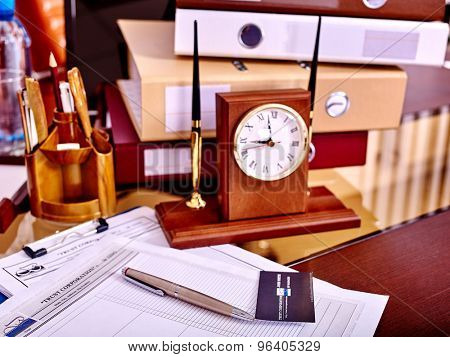 Business still life with stationery and clock on table in office.