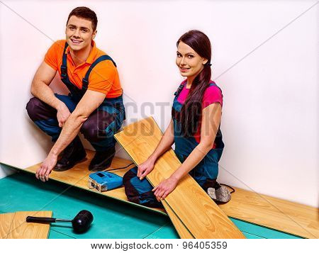 Happy family sitting on floor and laying parquet at home.