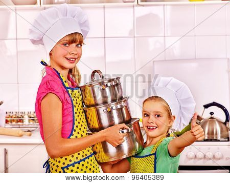 Children wearing hat and apron cooking at kitchen and show thumb up.