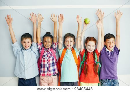 Row of ecstatic schoolmates with raised arms looking at camera