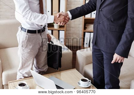 Successful businessmen handshaking after signing contract in office