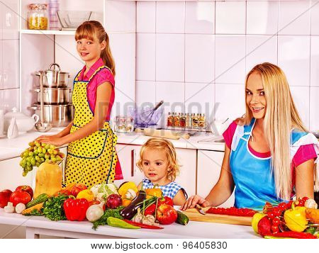 Mother and two beautiful  daughter cooking food at kitchen.