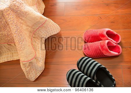 Two Pairs Of White Slippers On Floor Nearby A Bed