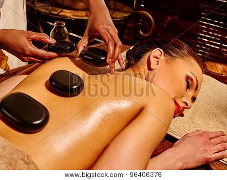 Young woman with three big stones having Ayurveda massage.