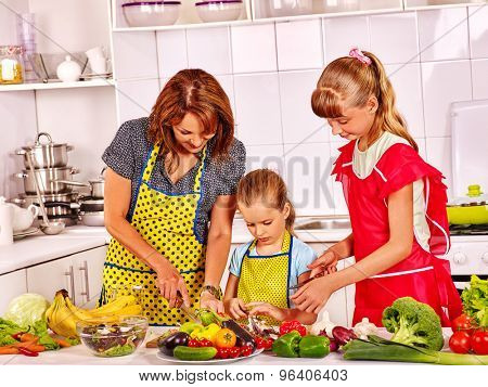 Happy mother and two girl children cooking at kitchen.