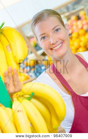 Shop assistant holding bananas