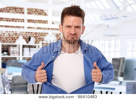 Aggressive man tearing shirt apart on his chest, looking wild.