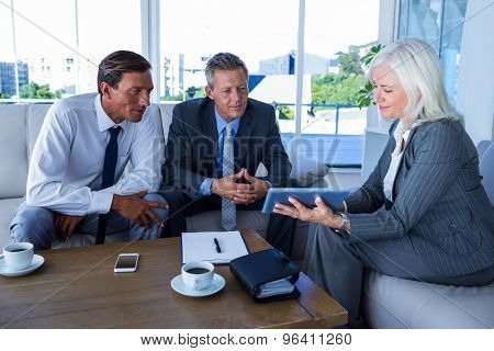 Business people looking at tablet computer in office