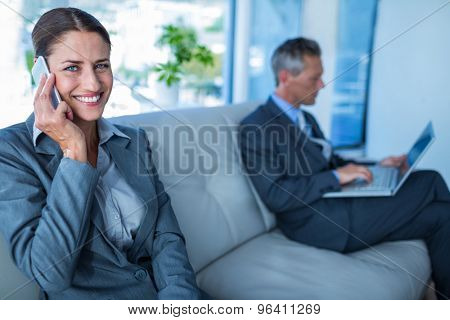 Businesswoman having phone call while her colleague using laptop in office