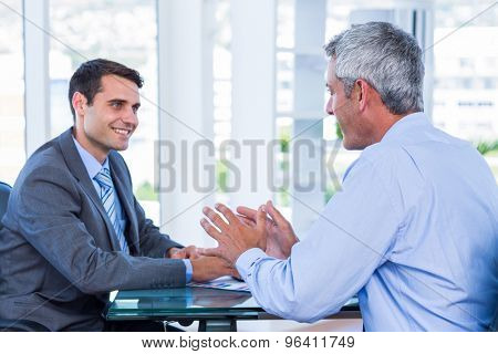Happy business people speaking together in office