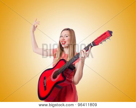 Woman playing guitar against the gradient