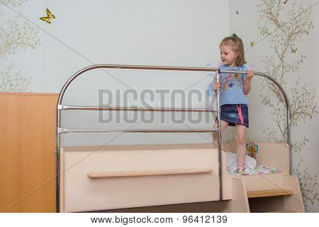 Little Girl Climbs On The Bed Holding The Handrail