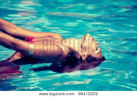 young attractive woman in  in pool with head thrown back side view