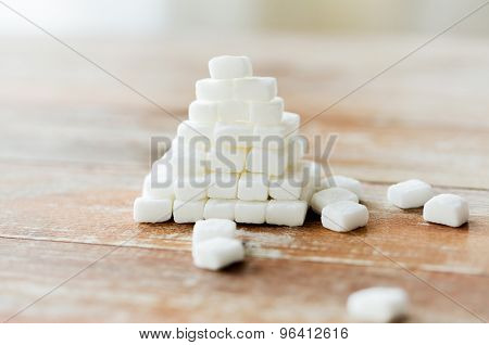 food, junk-food, cooking and unhealthy eating concept - close up of white sugar pyramid on wooden table