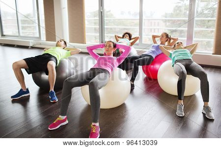 fitness, sport, training and lifestyle concept - group of people flexing abdominal muscles on fitball in gym
