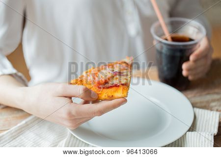 fast food, people and unhealthy eating concept - close up of woman hands with pizza and drink sitting at table