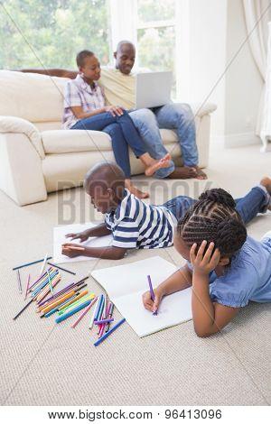 Happy siblings on the floor drawing in the living room