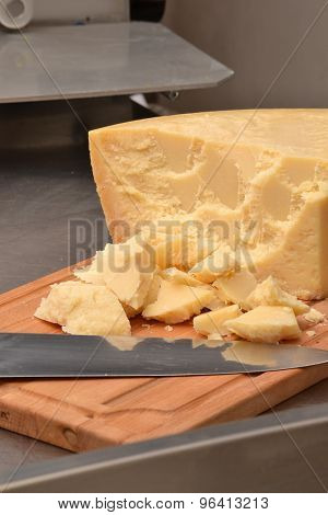 Chunks of parmesan cheese stack on wood table.