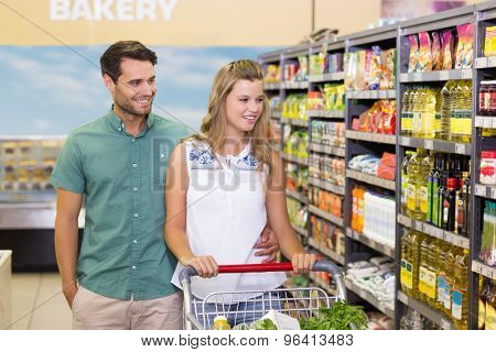 Bright couple buying products in aisle at supermarket