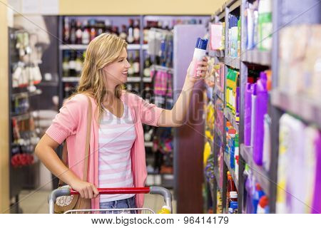 Smiling pretty young woman buying a products in supermarket