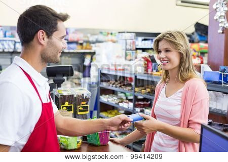 Side view of a smiling woman at cahg register paying with credit card in supermarket