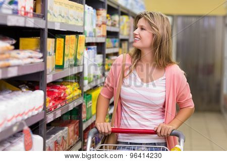 Smiling pretty blonde woman looking at shelf and buying a products in supermarket