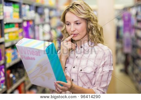 Smiling pretyt blonde woman reading on a box in a supermarket