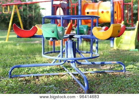 Colorful Roundabout With Yellow Chairs In Empty Child Playground
