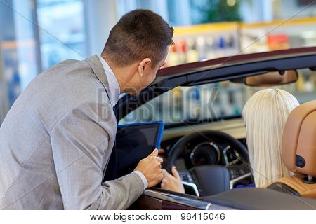 auto business, car sale, technology and people concept - woman and car dealer with tablet pc computer in auto show or salon