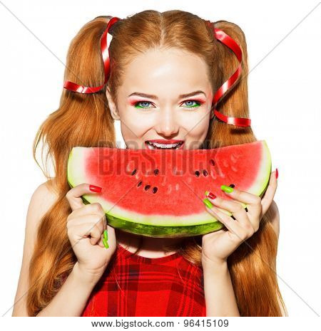 Beauty teenage model girl eating watermelon. Bright vivid makeup and manicure. Beautiful young woman holding slice of fresh ripe juicy watermelon and smiling, isolated on white background. pigtail